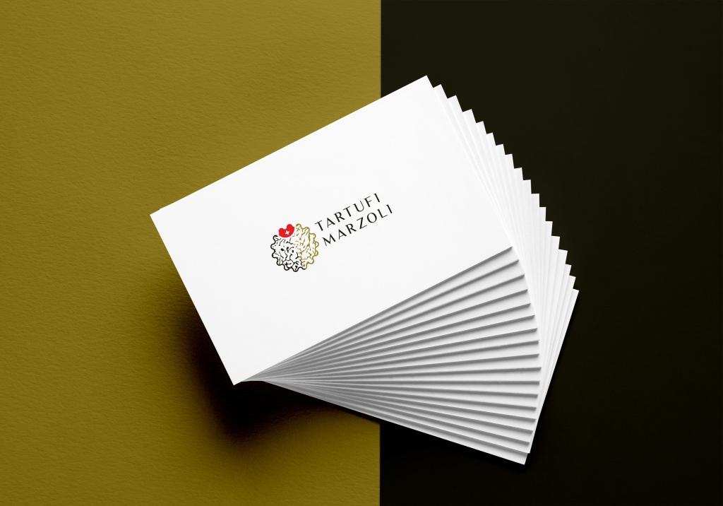 A business card mockup with the Tartufi Marzoli logo on it.